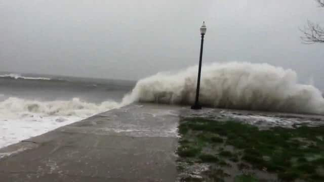 A large wave crashes at Seaside Park in Bridgeport, causing floods during a previous storm.