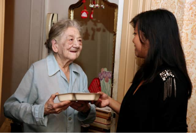 A client receives her meal from a volunteer of Pascack Valley Meals on Wheels.