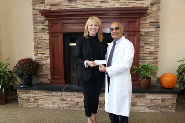 Dr. Hansraj Sheth, vice president of the medical staff, delivers check to Mary Young, CEO of the Red Cross Metro NY North chapter.