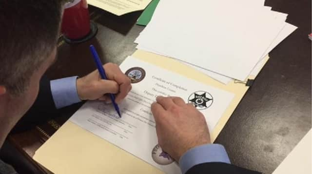 Dutchess County Evecutive Marc Molinaro signs certificates for 17 law enforcement officers who recently underwent training in crisis intervention.