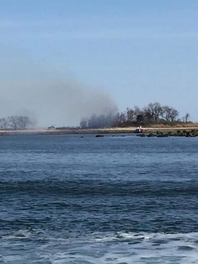 The brush fire on Grassy Island off the coast of Norwalk can be seen from the mainland.