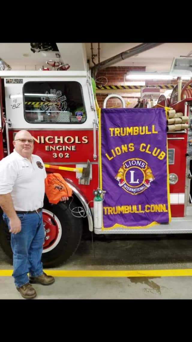 Assistant Fire Chief John DelVento of the Nichols Fire Department accepts a donation of pet oxygen masks from the Trumbull Lions Club.