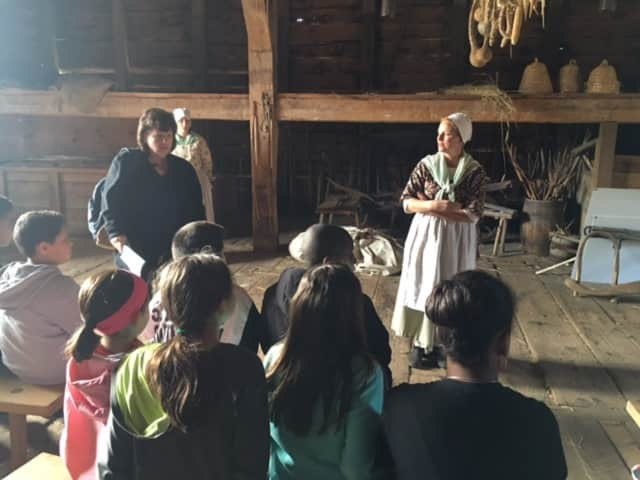 Tour guides dressed in period costumes at Philipsburg Manor talk to the visiting students.