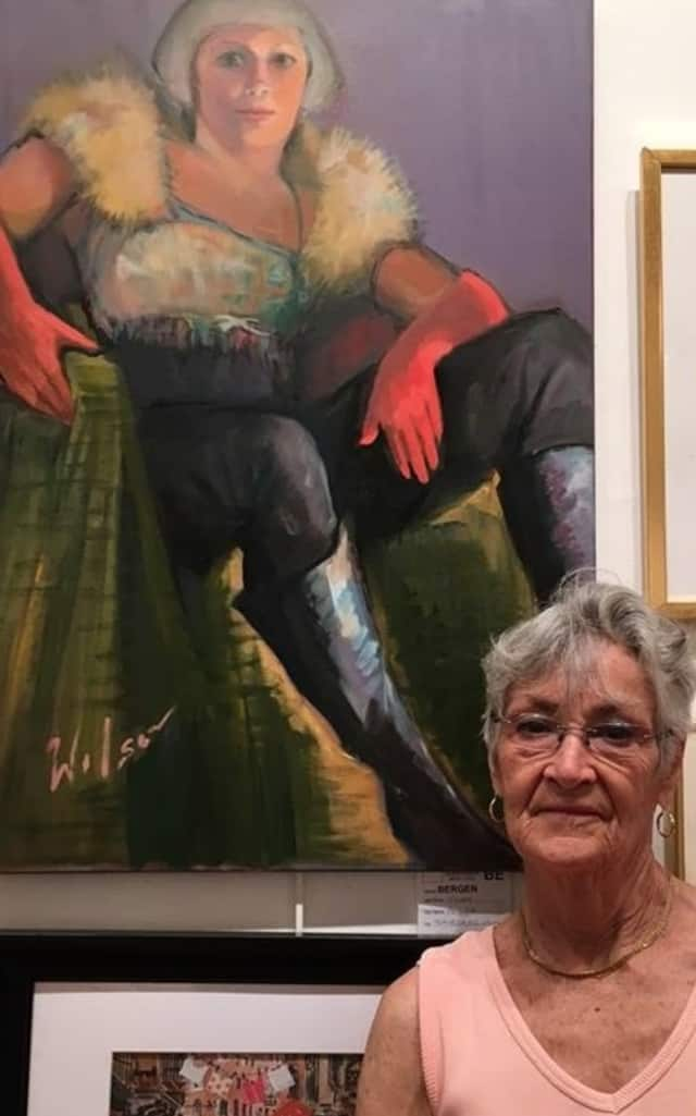 "Pat Wilson, of Teaneck, stands with her oil portrait, ""Bobbie in Red Gloves."""
