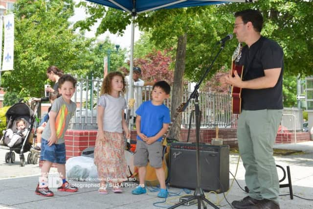 Children enjoy listening to music on the opening day of the New Rochelle Grand Market.