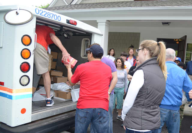Local volunteers help a postal worker unload a truck of donated food at Darien's Person-to-Person facility on May 11 during the 21st annual National Association of Letter Carriers Stamp Out Hunger food drive.