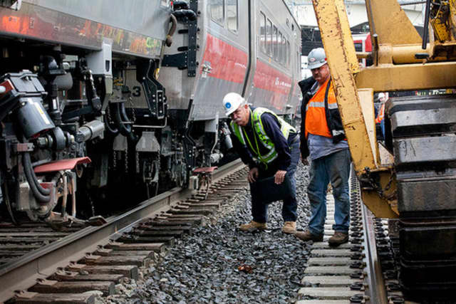 Rail workers inspect the area of the May 17 train derailment and collision along the Bridgeport/Fairfield border.