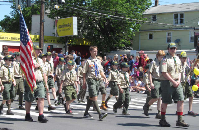 A group of Boy Scouts makes its way up a parade route.