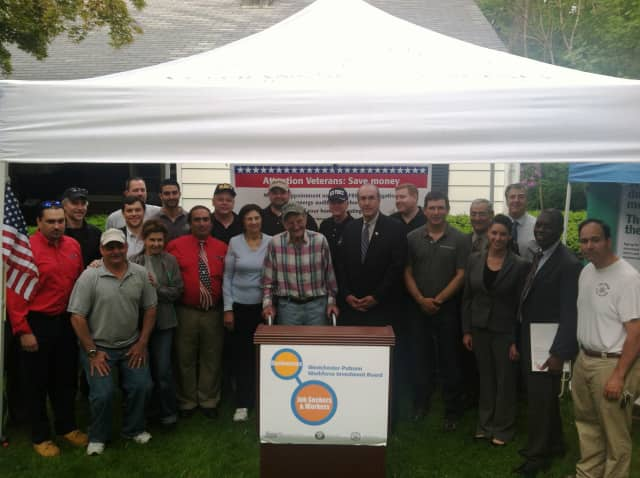 Ossining veteran Victor Paolantonio and his wife, center, are surrounded by local contractors who donated more than $20,000 in energy upgrades to the couple's home.