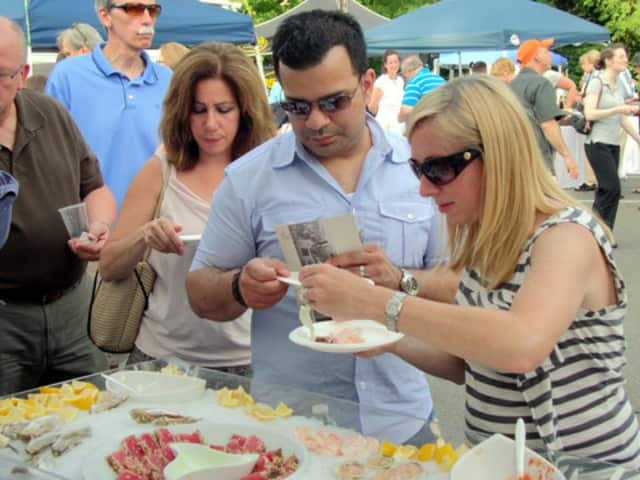 People try samples of food during a past year's Taste of Wilton event.