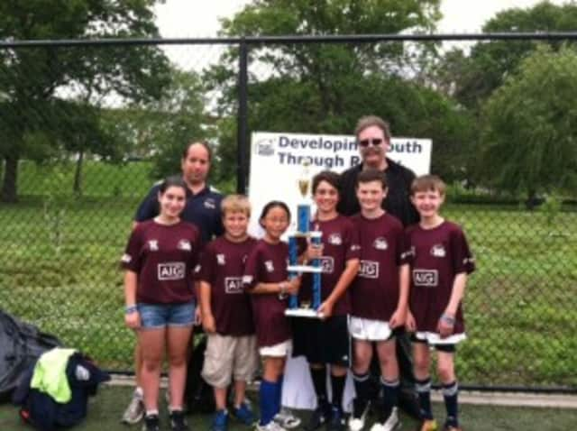 The Pelham elementary flag team and coaches held their trophy for winning the NYC Cup Division.