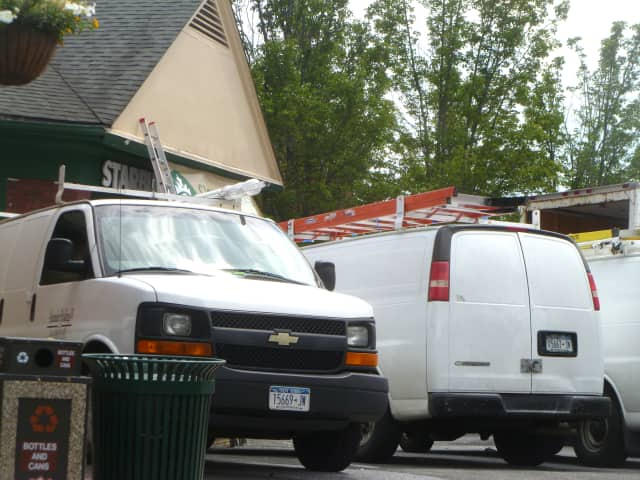Six white trucks were parked outside of the New Canaan Starbucks where renovations are under way.