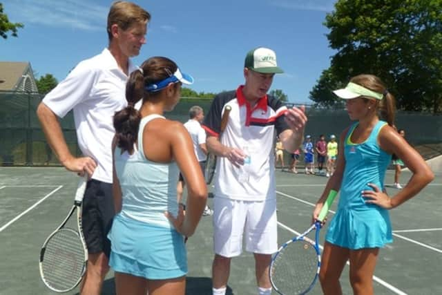 Peter Fleming and John McEnroe talk with Westchester tennis players Alexandra Sabe of Rye and Christina Sisti of Mout Vernon in Eastchester at the academy last year.