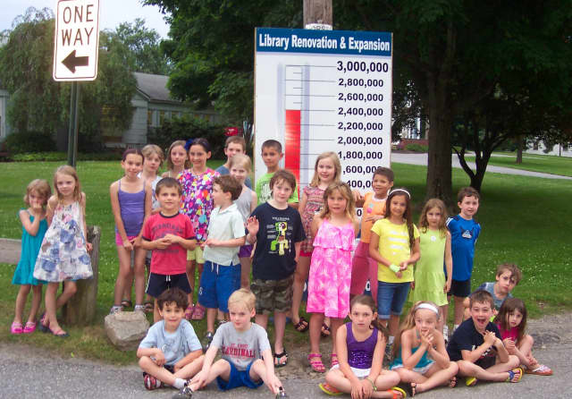 Children attending the Lewisboro Library's Summer Reading Kick-off Treasure Hunt pose by the Building Campaign's Fund-raising Thermometer.