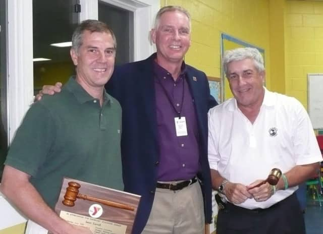 Wilton Family Y Executive Director Bob McDowell, center, greets Sean Carroll, past president of the Wilton Y Board of Directors, left, and newly elected board President Howard Steinberg, right.