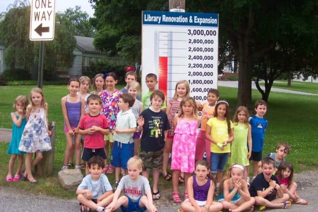 Children attending the Lewisboro Library's Summer Reading Kick-off Treasure Hunt pose by the Building Campaign's Fund-raising Thermometer