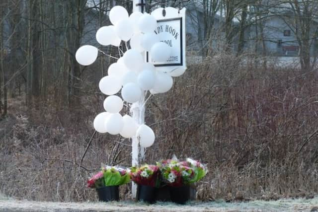 Balloons at the Sandy Hook School sign in Newtown, where 26 students and teachers were killed in a shooting nearly five years ago.