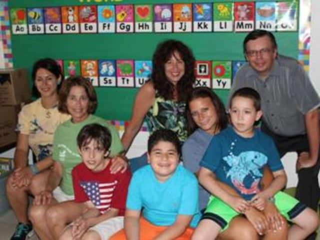 "Rose Rothe (center), executive director of SPARC, Inc., and Marcel Hegglin (right), United Way of Northern Westchester Local Presence Chair, with the kids and staff of the ""Summer Magic"" program at the Bedford Village Elementary School."