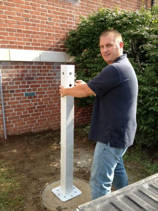 Neil Rea, project manager of Electrical Services Group, installs a Bruce Bennett Nissan-branded LEAF Charging Station at The Ridgefield Playhouse this week.