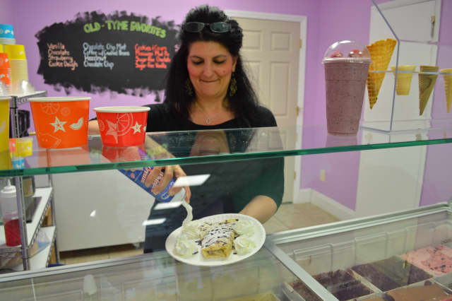 Maggie Nader, of Maggie May's Frozen Yogurt, adds the finishing touches on a sweet crepe, the latest addition to the Pound Ridge dessert shop's menu.