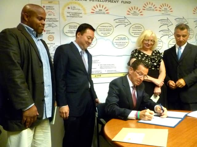 From left: Jerome Murray, State Rep. William Tong, Joan Carty, president of Housing Development Fund, and State Sen. Carlo Leone watch Gov. Dannel Malloy sign a new foreclosure bill into law.