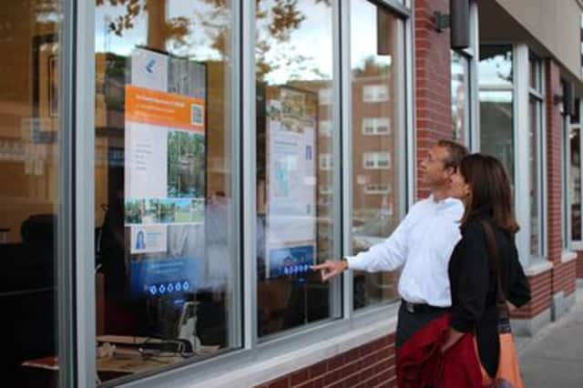 A couple checks out an interactive storefront for real estate information. Houlihan Lawrence will have the new technology at four Westchester locations.
