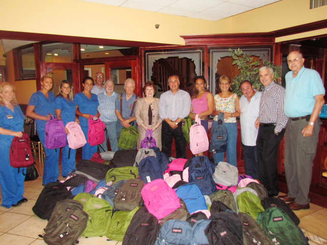 Workers collect fully stocked backpacks for children in Andrus programs,