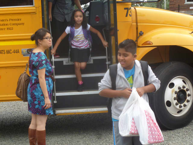 Dixson Elementary School students bounce off the bus on opening day of school.