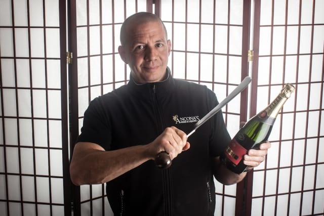 Mitch Ancona of Ancona's Wines & Liquors in Ridgefield will try for a world record in opening the most wine bottles in a minute with a saber.