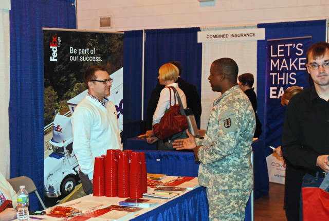 "National Guard Sgt 1st Class Byron Barnes speaks with an employer representative during a ""Hire our Heroes"" job fair in Rochester earlier this year."