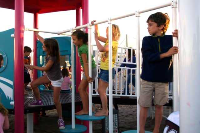 Children play on the new playground built in memory of Jessica Rekos on Fairfield's Penfield Beach after its grand opening Saturday.