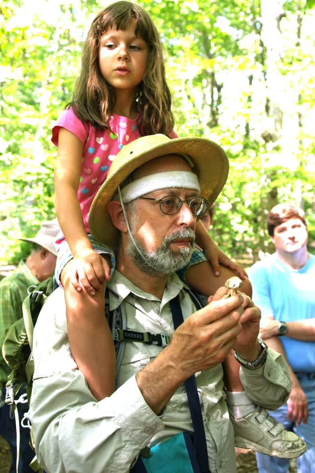 (File Photo) Steve Brill multi-tasks, teaching the crowd about wild mushrooms while giving his daughter Violet a rest.