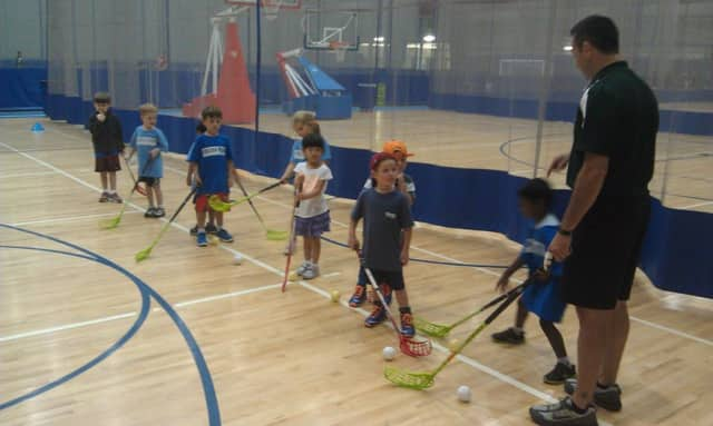 Greg Janos, right, teaches Floorball to children during a clinic at Chelsea Piers Connecticut in Stamford earlier this year.