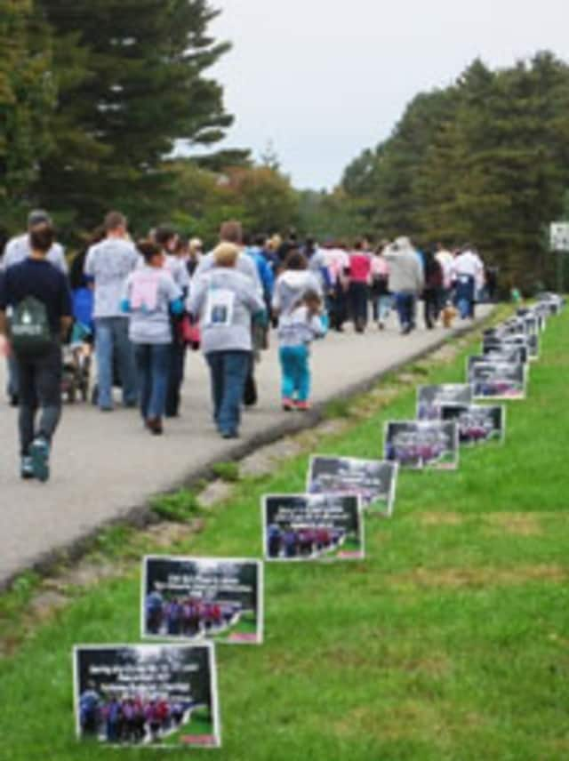 Walkers pass tribute signs along the Walk-A-Thon route.
