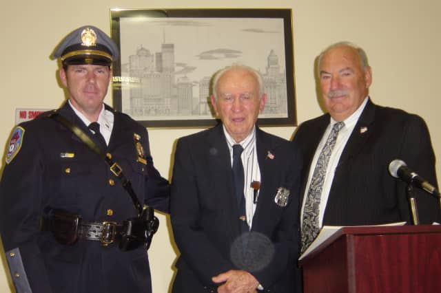 Lieutenant Michael Cindrich, left, and Mt. Kisco Mayor Michael Cindrich, right, present John Hvisch with his police badge after a 38-year oversight.