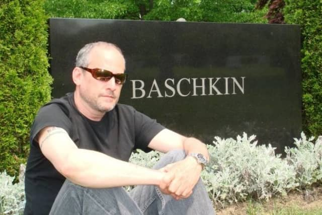 Laurance Baschkin sits by the headstone of family members. There are 18 cemeteries in Pound Ridge.
