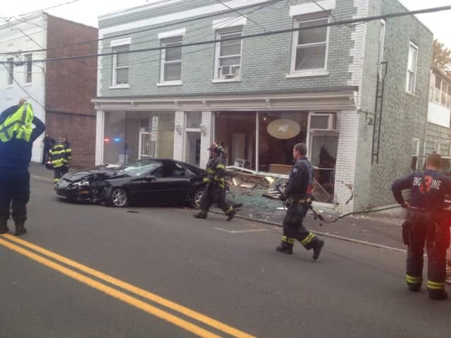 Greenwich firefighters respond after a Camaro slammed into a business on Pemberwick Road.