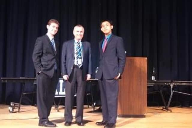 Blind Brook High School students Samuel Zarkower and Stanley Vuong pose with Superintendent of Schools William Stark following the Friday debate.