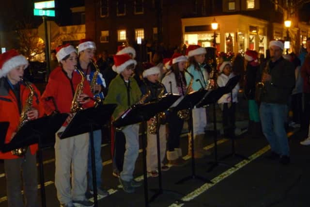 Saxe Middle School students play holiday tunes on their saxophones under the direction of Chris Coulter, right at the 2012 Holidy Stroll.
