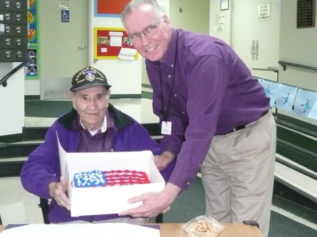 Wilton Family Y volunteer Al Mecozzi, a World War II veteran, receives a cake from Y Executive Director Bob McDowell Monday in honor of his military service.