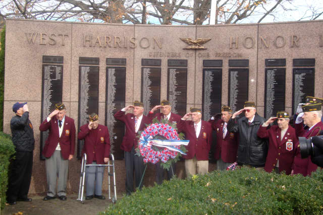 Veterans salute during Taps at the ceremony held on the West Harrison Village Green following the Veterans Day parade.