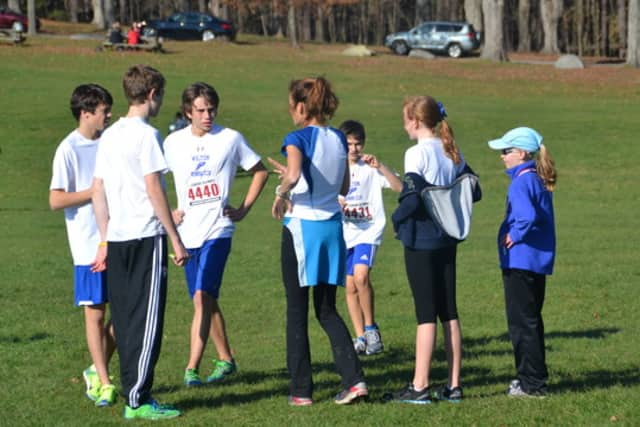 Wilton Running Club coach Mary Zengo talks with young runners during a meet last year.