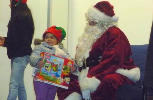 Santa hands out gifts to children during a previous visit to Port Chester.