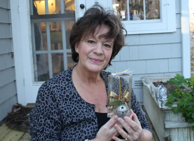 Laurie Davis displays one of this year's 2013 ornaments outside her Wilton studio.