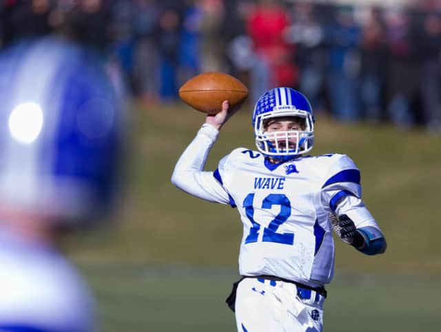 Darien quarterback Silas Wyper throws to a receiver during the Blue Wave's win over New Canaan on Thanksgiving.