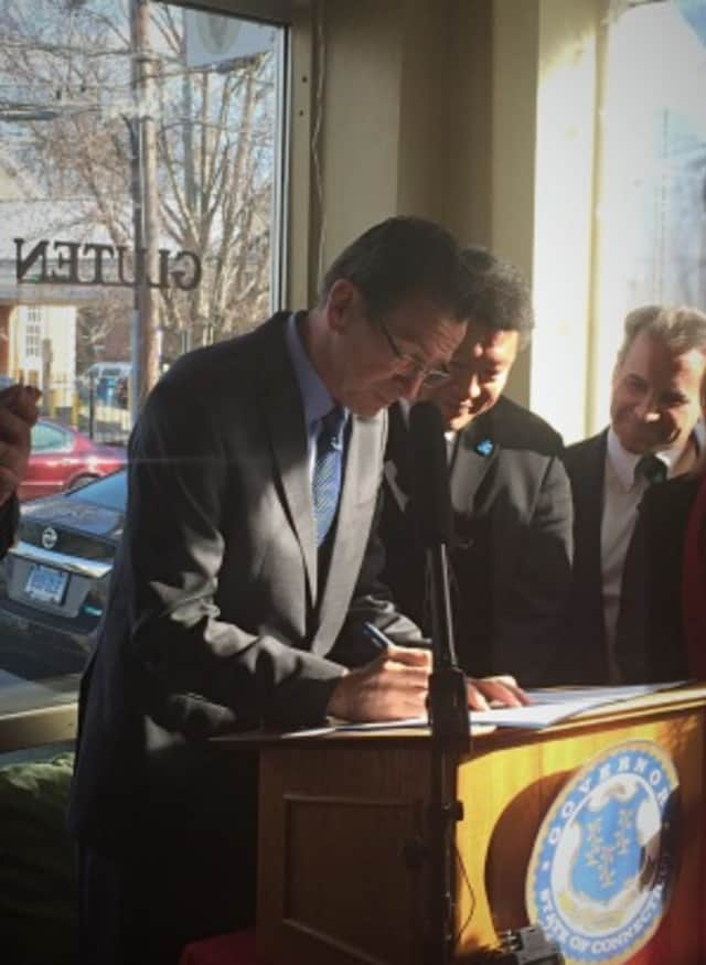 Gov. Dannel Malloy signs the GMO labeling law in Fairfield's Catch A Healthy Habit Cafe with local lawmakers and supporters.