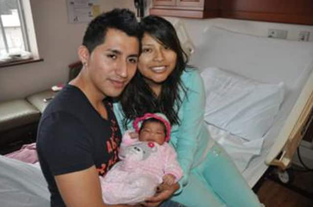Alex Quiroga (left) and Marcela Ona (right) of Peekskill hold their first born, baby Ayleen.