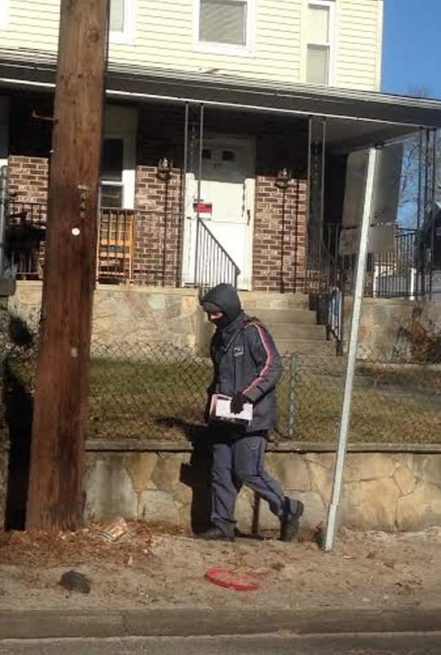 This mailman knows to bundle up on a frigid and windy day.