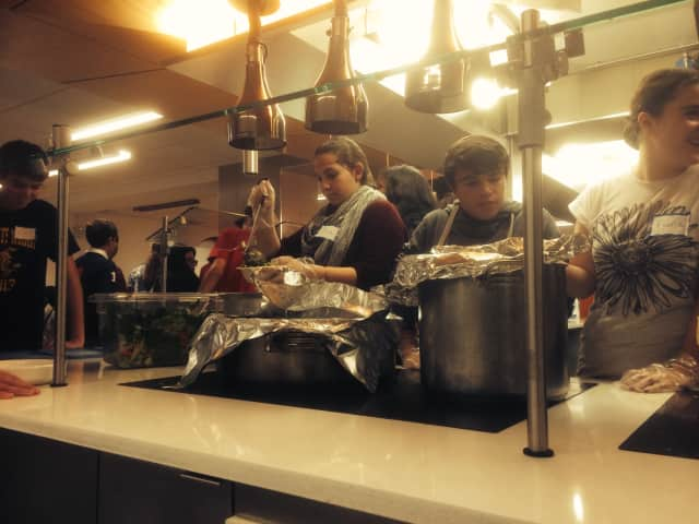 Liam Tobin works with his classmates to serve dinner to the homeless in New York City.