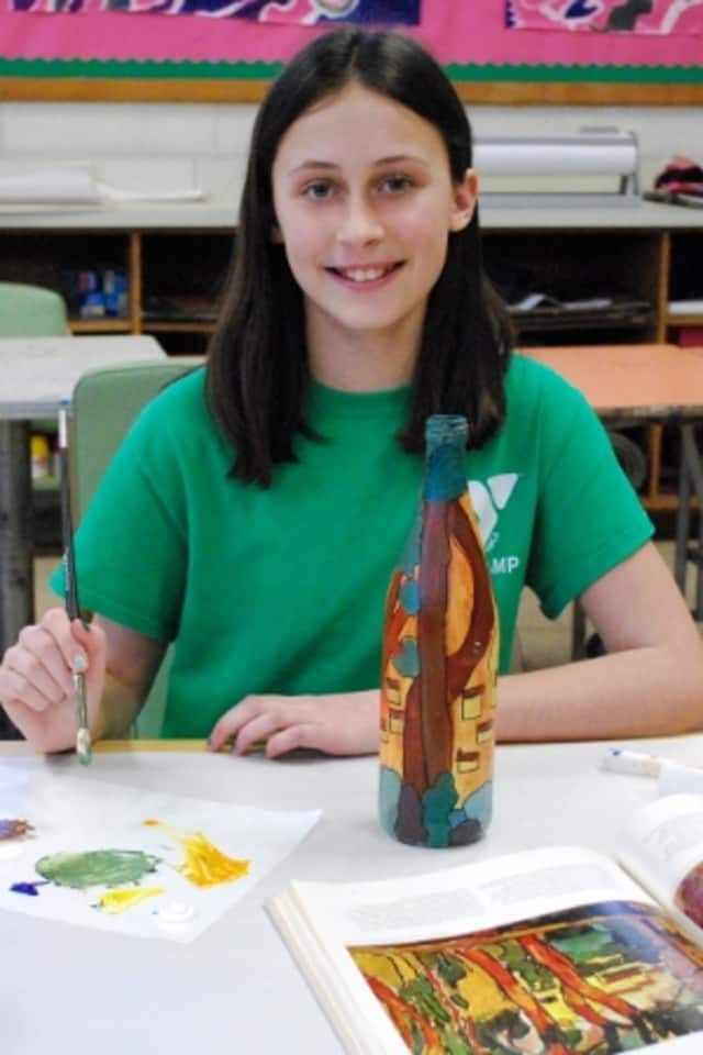 """Darien Arts Center student Jenna Funkey puts the finishing touches on her artwork, which will be featured in the """"Drawn to Nature"""" Art Show at the Darien Nature Center during February."""